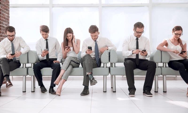 Grupa młodzi pracownicy siedzi z rzędu w biurowej poczekalni zdjęcie royalty free