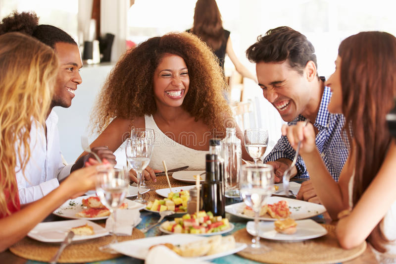 Grupa Młodzi przyjaciele Cieszy się posiłek W Plenerowej restauraci zdjęcia stock