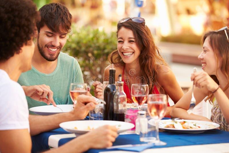 Grupa Młodzi przyjaciele Cieszy się posiłek W Plenerowej restauraci obraz royalty free
