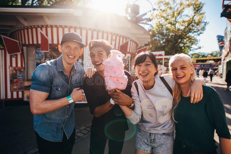 Grupa młodzi przyjaciele z bawełnianym cukierkiem w parku rozrywki obrazy royalty free