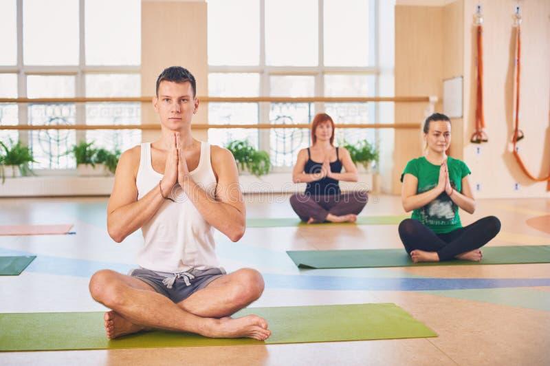 Grupa młodzi sporty ludzie ćwiczy joga lekcję z instruktorem, siedzi w Padmasana ćwiczeniu, Lotosowa poza z fałdowymi rękami ja zdjęcia stock
