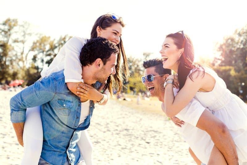 Grupa młodzi szczęśliwi ludzie niesie kobiety na piaskowatej plaży zdjęcia stock