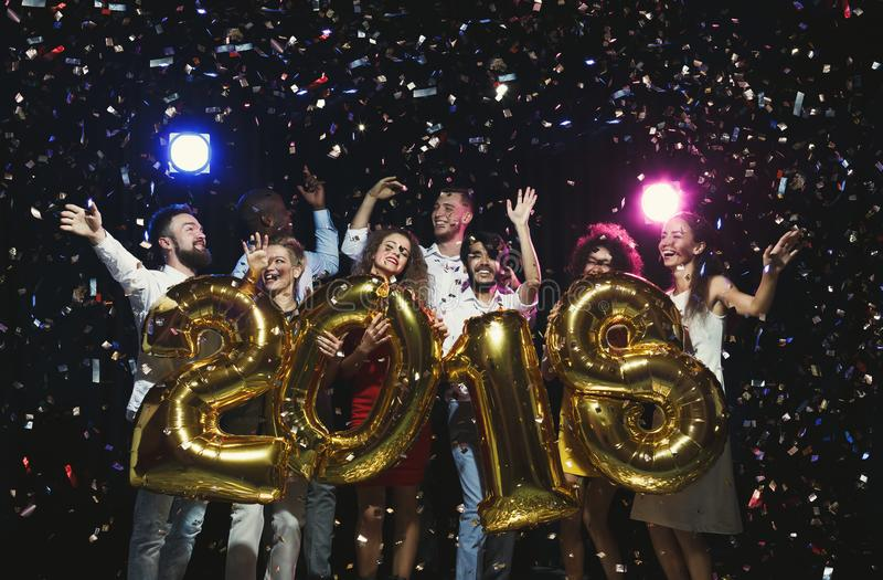 Grupa młodzi szczęśliwi przyjaciele z numerowymi balonami przy nowego roku przyjęciem obraz stock