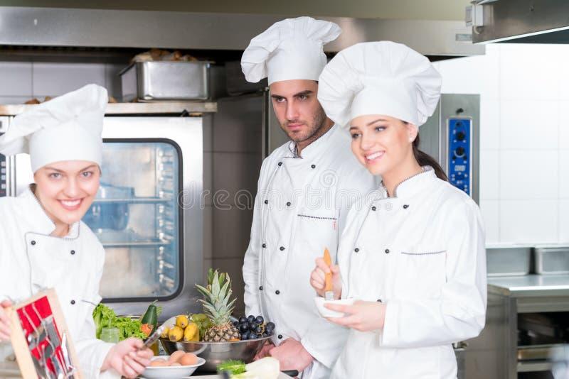 Grupa młodzi szefowie kuchni prepairing posiłek w luksusowej restauraci obraz royalty free