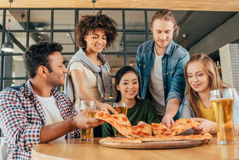 Grupa młodzi wieloetniczni przyjaciele ma pizzę fotografia royalty free