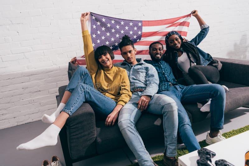 grupa młodzi wielokulturowi przyjaciele siedzi na leżance z flagą royalty ilustracja