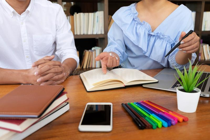 Grupa m?odzi ludzie uczy si? studiowanie lekcj? w bibliotece podczas pomaga? ucz?cy przyjaciel edukacj? przygotowywa dla egzaminu obrazy royalty free