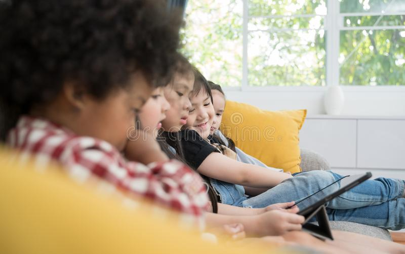 Grupa małe dzieci ogląda ekranową film kreskówkę wpólnie na cyfrowej pastylce Dzieciaki bawić się z pastylką z przyjaciółmi w dom zdjęcie royalty free