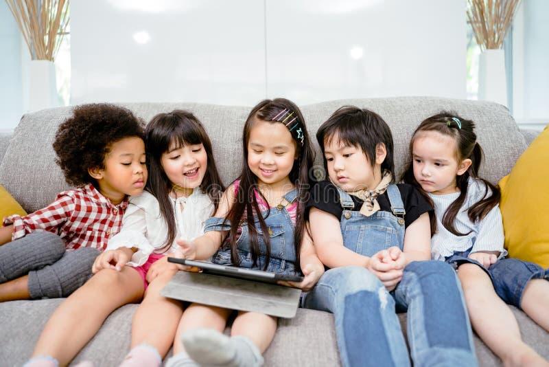 Grupa małe dzieci ogląda ekranową film kreskówkę wpólnie na cyfrowej pastylce Dzieciaki bawić się z pastylką z przyjaciółmi w dom zdjęcia royalty free