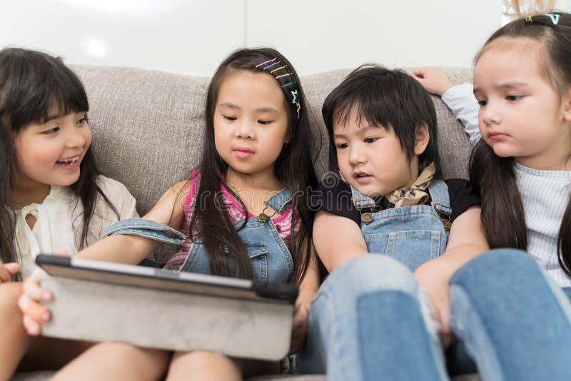 Grupa małe dzieci ogląda ekranową film kreskówkę wpólnie na cyfrowej pastylce Dzieciaki bawić się z pastylką z przyjaciółmi w dom zdjęcie stock