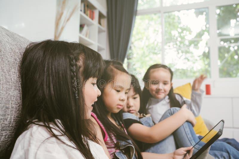 Grupa małe dzieci ogląda ekranową film kreskówkę wpólnie na cyfrowej pastylce Dzieciaki bawić się z pastylką z przyjaciółmi w dom obrazy stock