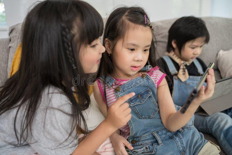 Grupa małe dzieci ogląda ekranową film kreskówkę wpólnie na cyfrowej pastylce i telefonie Dzieciaki bawi? si? z smartphone fotografia royalty free