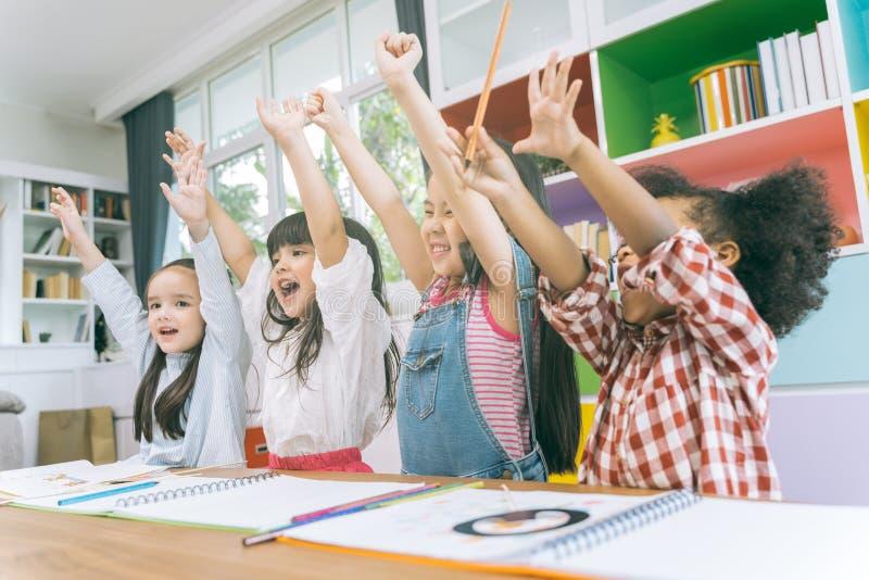 Grupa mały preschool żartuje ręki w w górę klasy portret dziecko różnorodności edukacji pojęcie zdjęcie stock