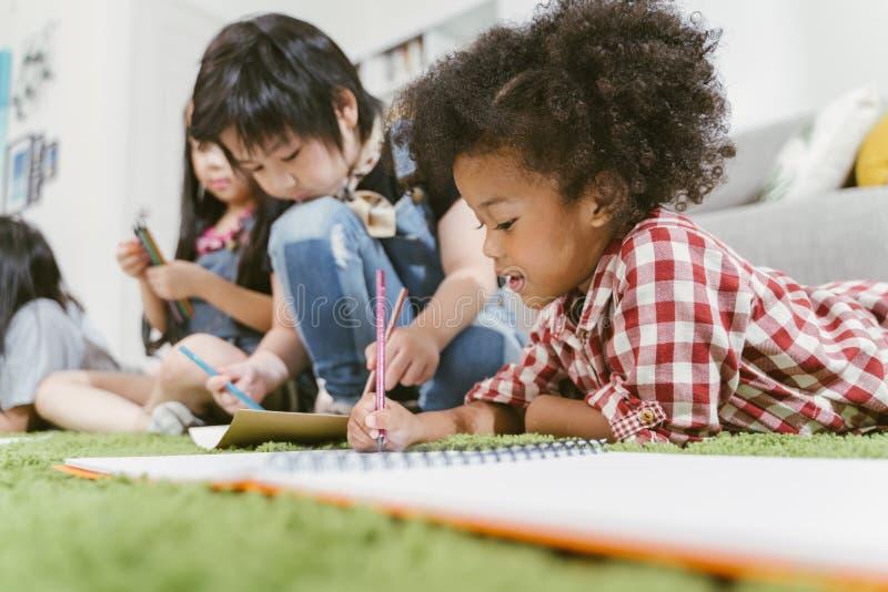 Grupa mały preschool żartuje rysunkowego papier z kolorów ołówkami portret Afrykańska dziewczyna z przyjaciel edukacji pojęciem obraz stock