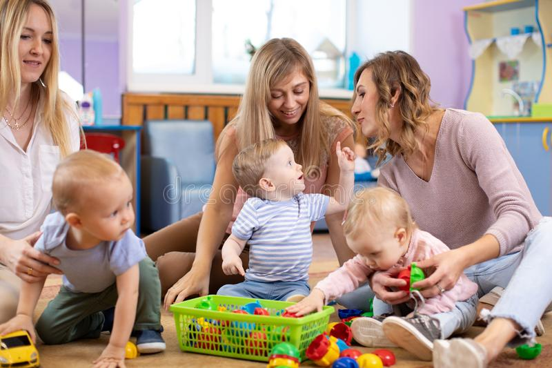 Grupa mamy i ich dzieci bawić się w opieki dziennej centrum zdjęcie royalty free