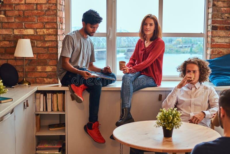 Grupa międzyrasowi ucznie odpoczywa w studenckim dormitorium zdjęcia stock