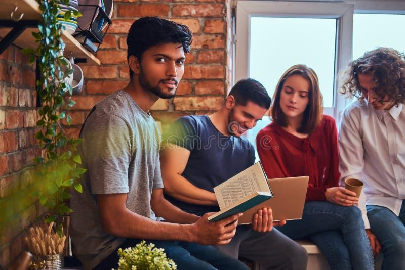 Grupa międzyrasowi ucznie z laptopem i książką robi lekcjom w studenckim dormitorium obrazy stock