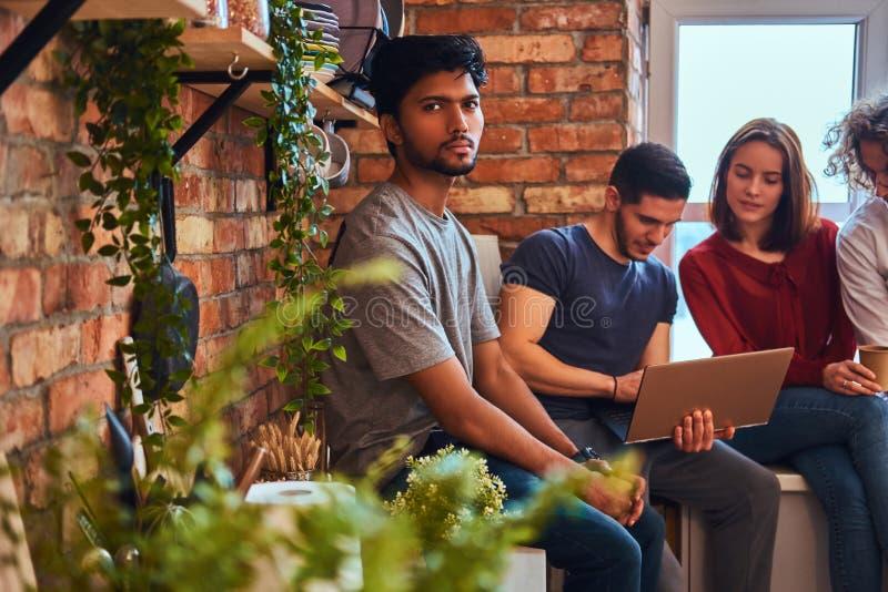 Grupa międzyrasowi ucznie z laptopem i książką robi lekcjom w studenckim dormitorium zdjęcie royalty free