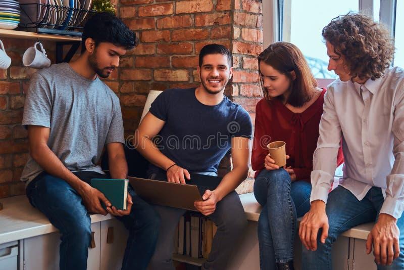 Grupa międzyrasowi ucznie z laptopem i książką robi lekcjom w studenckim dormitorium zdjęcia royalty free