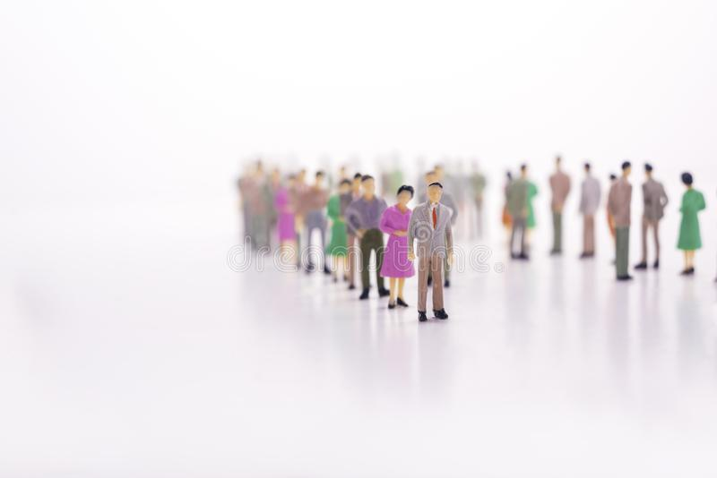 Grupa miniaturowi ludzie nad białą tło pozycją w linii obrazy stock