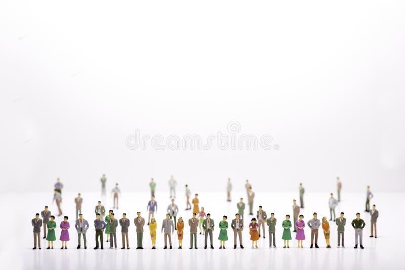 Grupa miniaturowi ludzie nad białą tło pozycją w linii zdjęcia royalty free
