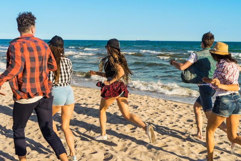 Grupa modnisiów młodzi przyjaciele biega wzdłuż plaży wpólnie zdjęcie royalty free