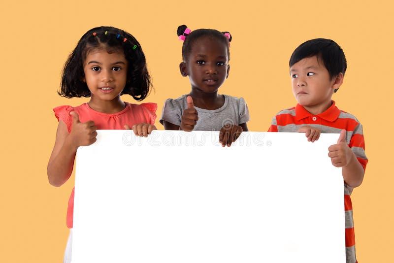 Grupa multiracial dzieciaka portret z białą deską obraz royalty free