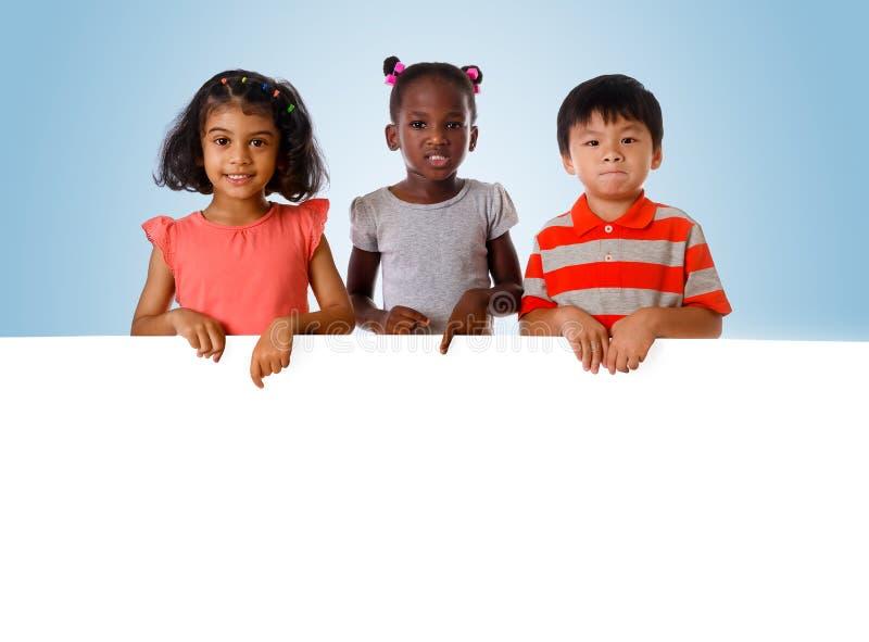 Grupa multiracial dzieciaka portret z białą deską obrazy royalty free