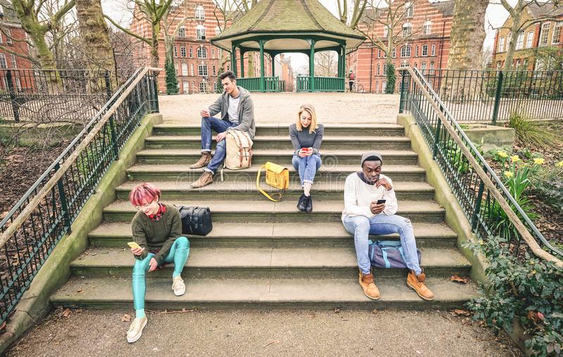 Grupa multiracial przyjaciele używa mobilnego mądrze telefon - nałogu pojęcie fotografia royalty free