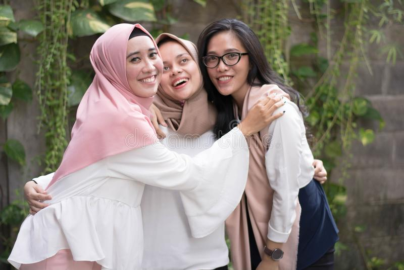 Grupa najlepszy belzebuba muzułmańska dziewczyna ono uśmiecha się przy kamerą podczas gdy ściskający obraz stock