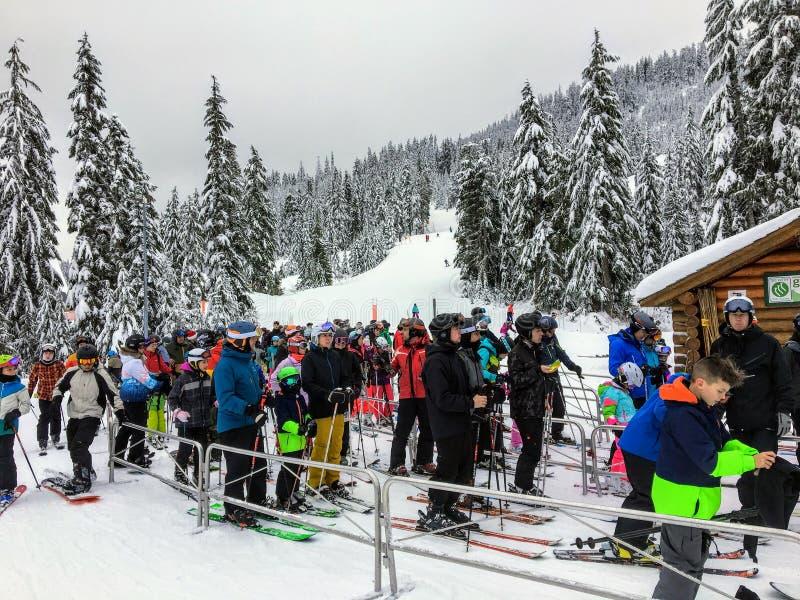 Grupa narciarki i snowboarders czeka w linii uczepiać się przejażdżkę w górę narciarskiego dźwignięcia na Cyprysowej górze fotografia royalty free