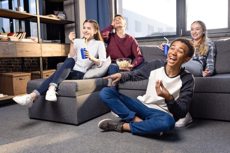 Grupa nastolatkowie ogląda film wpólnie w domu, nastolatkowie ma zabawy pojęcie obraz royalty free