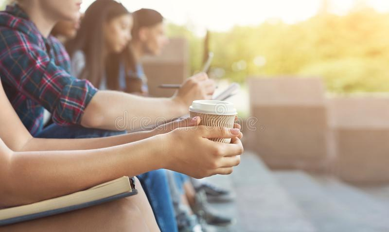 Grupa nastolatkowie siedzi outdoors, dziewczyna trzyma takeaway filiżankę obraz stock