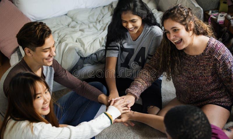 Grupa nastolatkowie stawia ich ręki społeczności i pracy zespołowej wpólnie w sypialni pojęcie zdjęcie royalty free