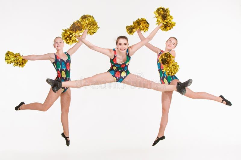 Grupa nastoletni cheerleaders skacze przy białym studiiem fotografia stock
