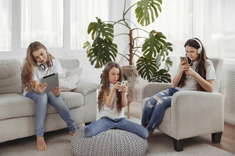 Grupa nastoletnie dziewczyny używa gadżety Dzieciaki z telefonami, pastylki, smartphones i hełmofony, zdjęcie royalty free