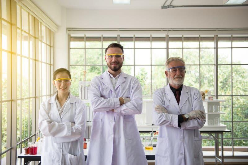 Grupa naukowów ludzie stoi wpólnie w laboratorium i krzyż ręki, Pomyślny pracy zespołowej pojęcie zdjęcia stock