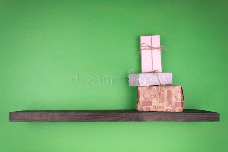 Grupa nowy rok prezenty składał jeden na inny na półce ciemny kolor który załatwia na ścianie zieleń obraz stock