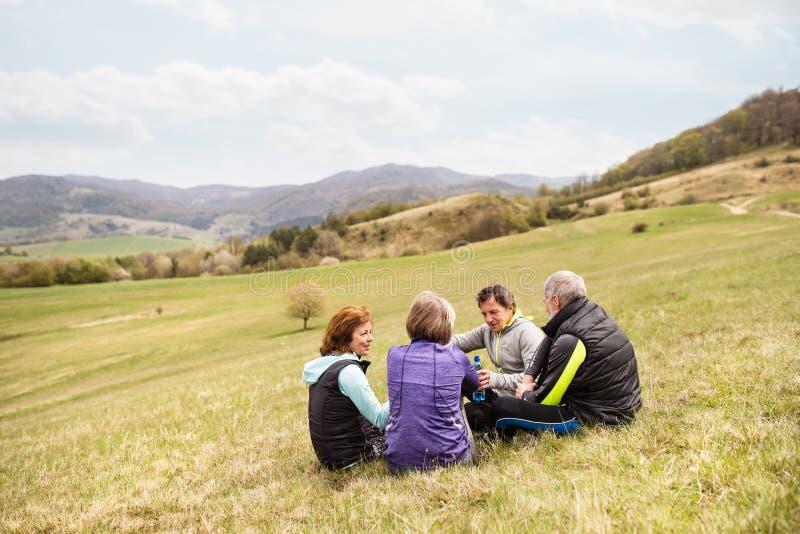 Grupa odpoczywa i opowiada starsi biegacze outdoors, obraz royalty free