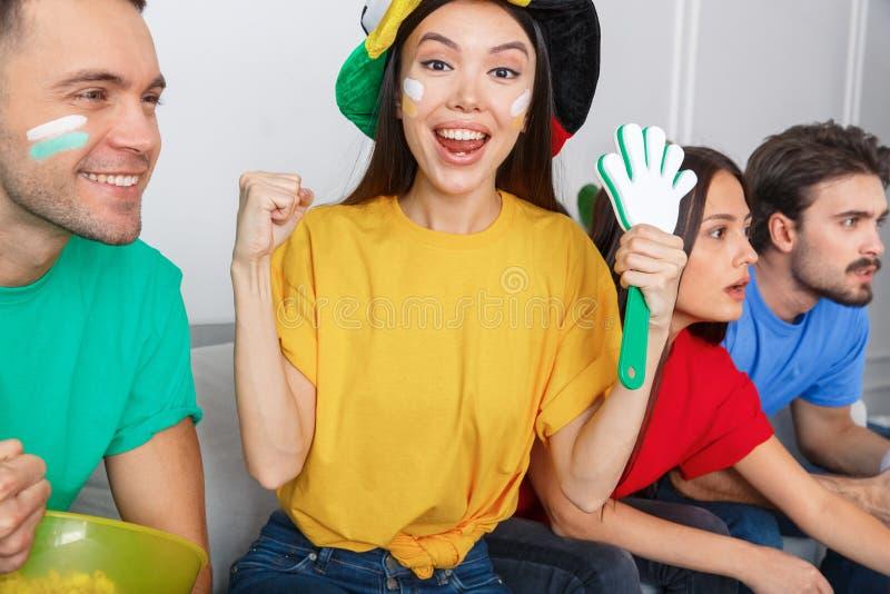 Grupa ogląda dopasowanie w kolorowej koszula dziewczyny kamery przyglądającym zakończeniu przyjaciół wielbiciele sportu zdjęcia royalty free