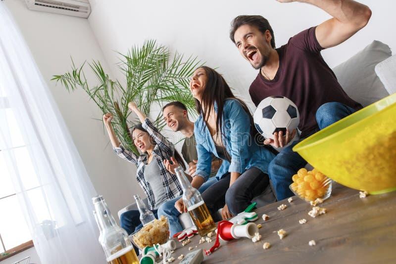 Grupa ogląda futbolowego dopasowanie przyjaciół wielbiciele sportu wręcza w górę rozochoconego zdjęcie royalty free