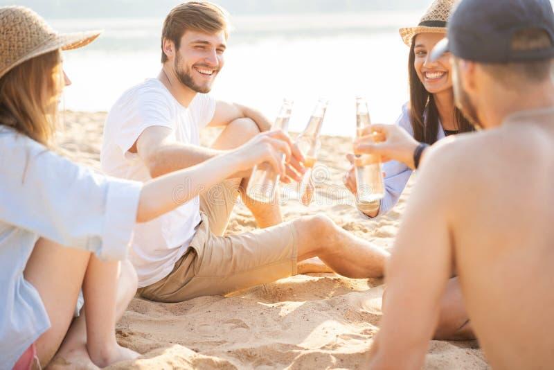 Grupa opowiada piwa i pije szcz??liwi m?odzi ludzie siedzi wp?lnie przy pla?? zdjęcie royalty free