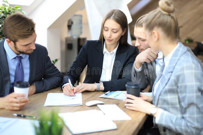 Grupa partnery biznesowi dyskutuje strategie przy spotkaniem w biurze obraz stock