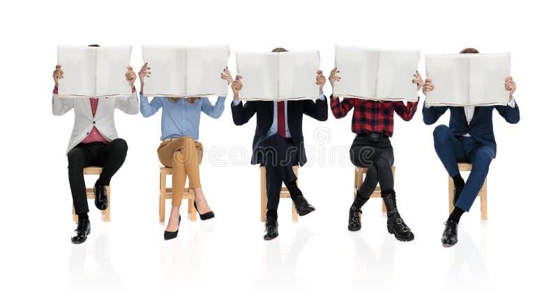 Grupa pięć młodzi ludzie siedzi gazety i czyta obraz stock