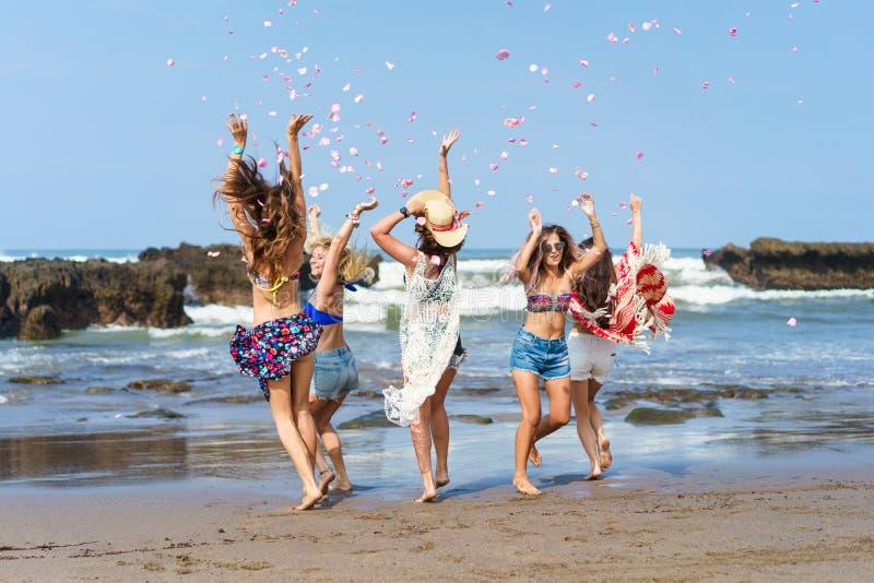 grupa piękne młode kobiety ma zabawę i rzuca w górę płatków obraz stock