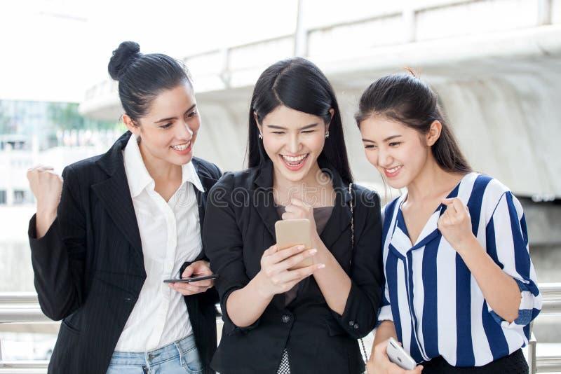 grupa piękni młoda kobieta przyjaciele używa mądrze telefon i śmiający się outdoors trzy dziewczyny podniecającego biznesowego on obraz stock