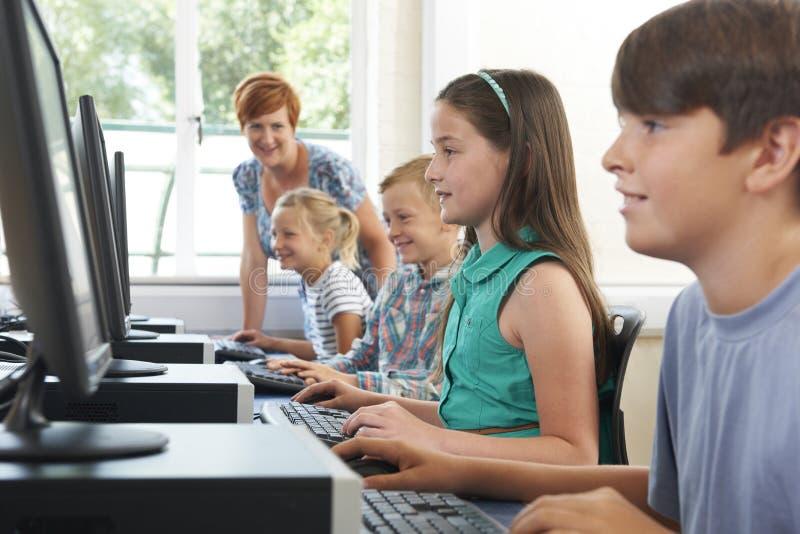 Grupa Podstawowi ucznie W komputer klasie Z nauczycielem fotografia stock