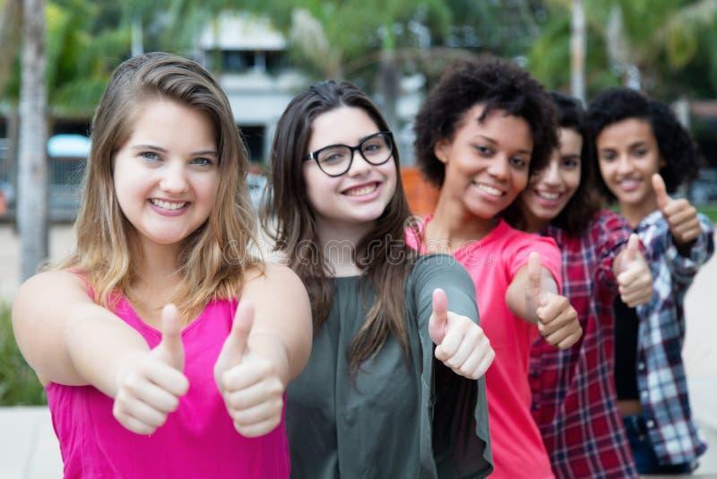 Grupa pomyślne międzynarodowe dziewczyny stoi w linii obraz stock