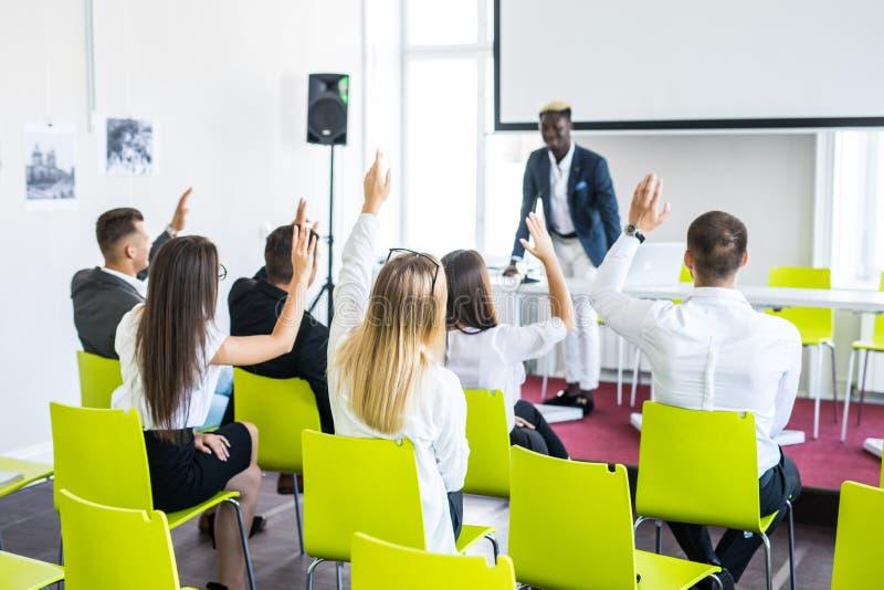 Grupa pomyślni ludzie biznesu pyta pytania podczas drużynowego konwersatorium przy wykładem zdjęcie stock
