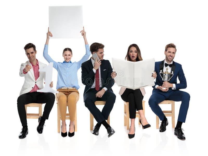 Grupa posadzeni ludzie robi różnym rzeczom obrazy royalty free